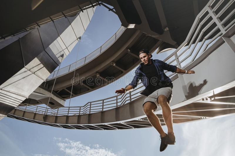Parkour athlete flying from high attitude. Man perform dangerous freerunning tricks royalty free stock image
