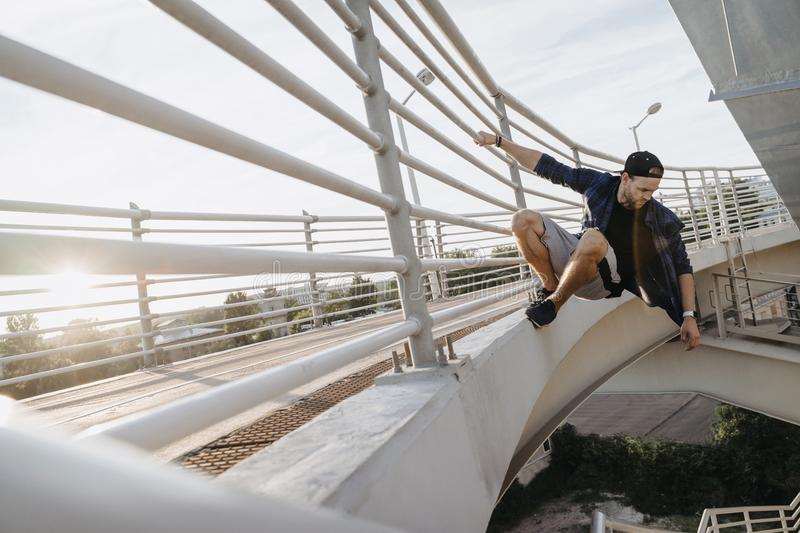 Parkour athlete hanging on the bridge and ready for dangerous jump. Freerunning in the city stock image