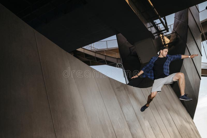 Parkour athlete jumping from the wall and flying. Man practicing freerunning stock photography