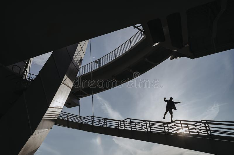 Parkour athlete performs a deadly stunt. Parkour athlete risk his own live performs a deadly stunt. Freerunning athlete walks along the railing at high altitude stock images
