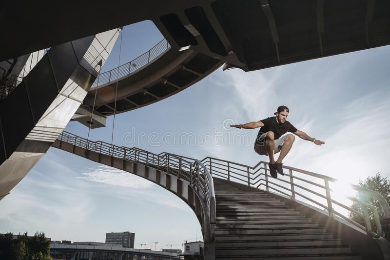 Parkour athlete training in the city. Man performs a big freerunning jump through the stairs stock image