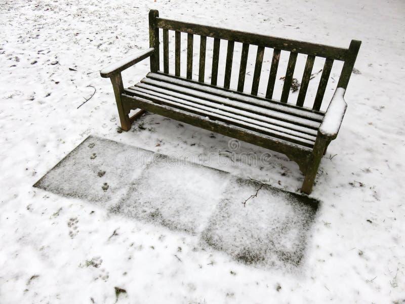 Parkowa ławka w śniegu w Marzec obrazy stock