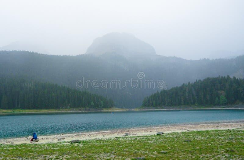 Parkowy Durmitor Montenegro B??kitny jezioro Czarny jezioro Mężczyzna siedzi jeziorem zdjęcie royalty free