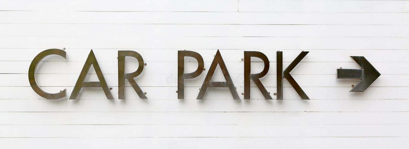 Parkplatzzeichen mit Pfeil auf weißer hölzerner Planke lizenzfreie stockfotos