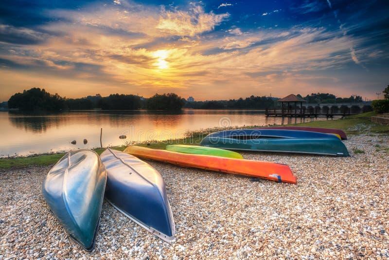 Parkujący czółna jeziorem przy zmierzchem obraz stock