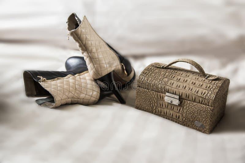 Parkvinnligkängor och handväska över vit royaltyfri bild