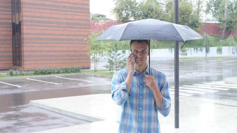 Parlando sul telefono, stante sotto l'ombrello durante la pioggia immagine stock