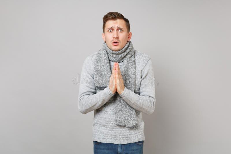 Parlant en faveur le jeune homme dans le chandail gris, écharpe tenant des mains ensemble, priant sur le fond gris de mur Sain photographie stock