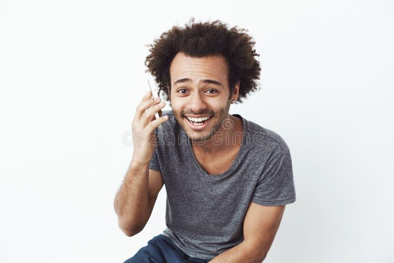 Parlare sorridente dell'uomo africano allegro sul telefono sopra fondo bianco immagine stock libera da diritti