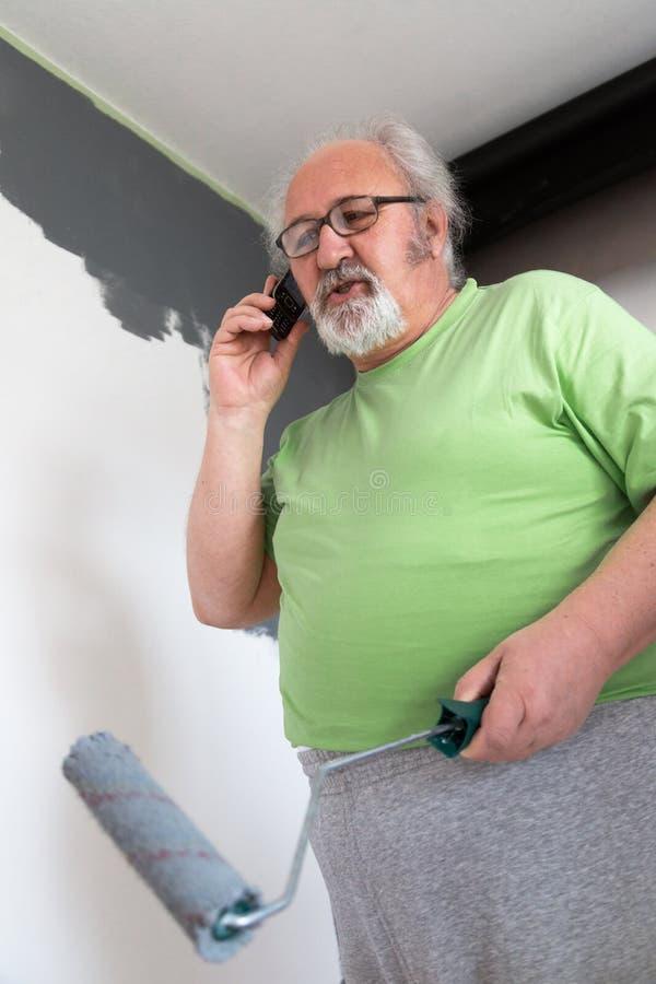 Parler au téléphone portable et peinture du mur photos stock