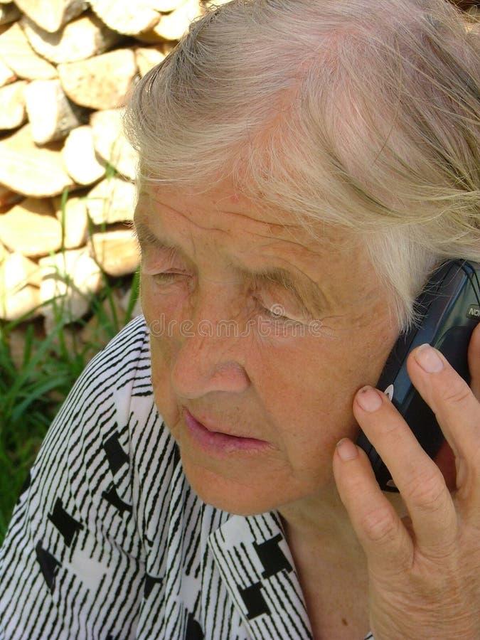 Parler avec un téléphone portable image stock