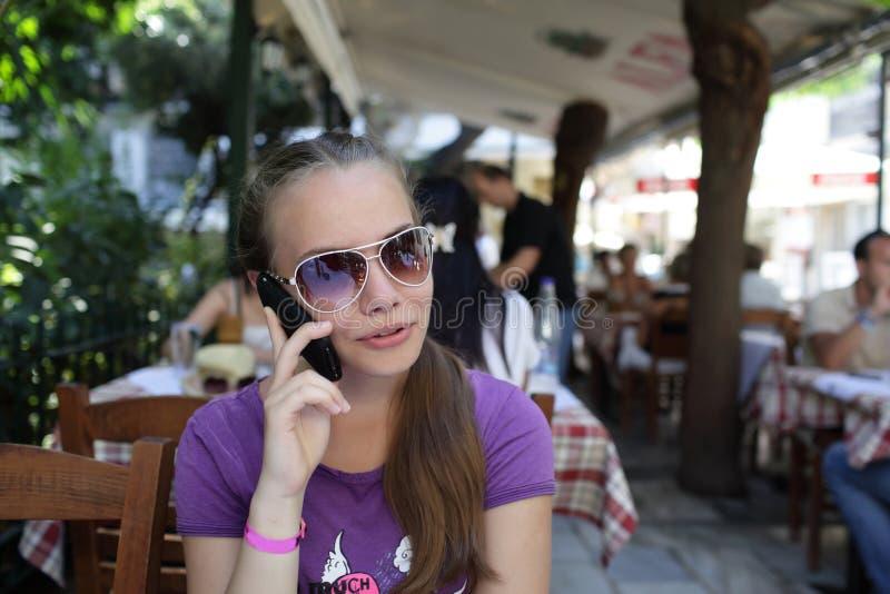 Parler de l'adolescence par le téléphone photo stock
