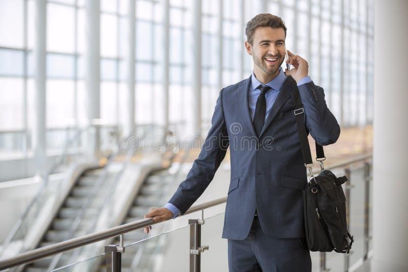 Parler de marche debout d'homme d'affaires à son téléphone portable photographie stock