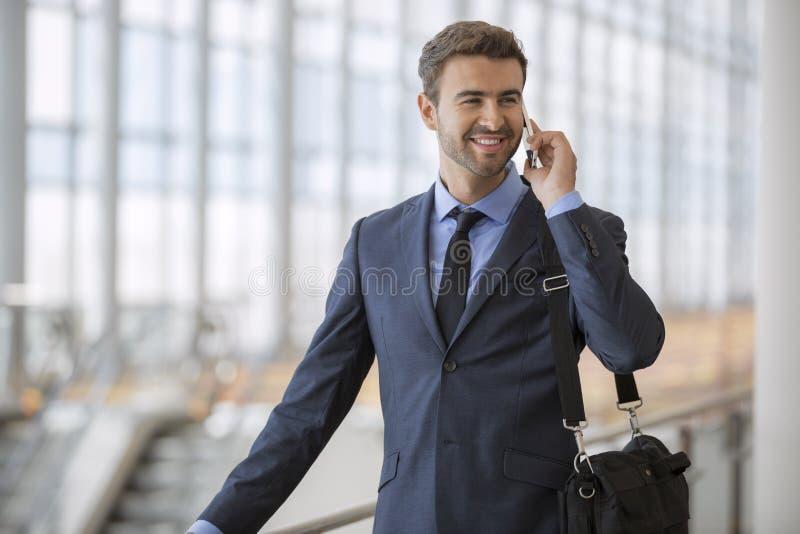 Parler de marche debout d'homme d'affaires à son téléphone portable image libre de droits