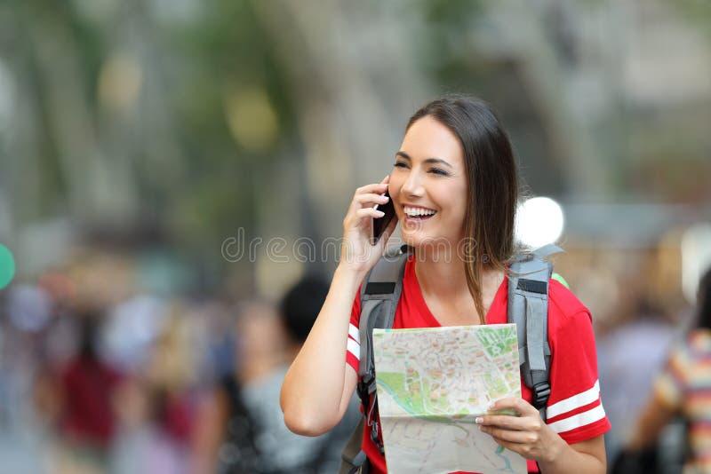 Parler de touristes adolescent au téléphone dans la rue photographie stock