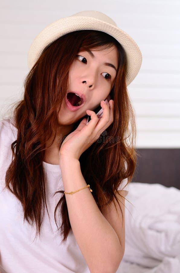 Parler et causerie adolescentes asiatiques avec le téléphone portable photographie stock