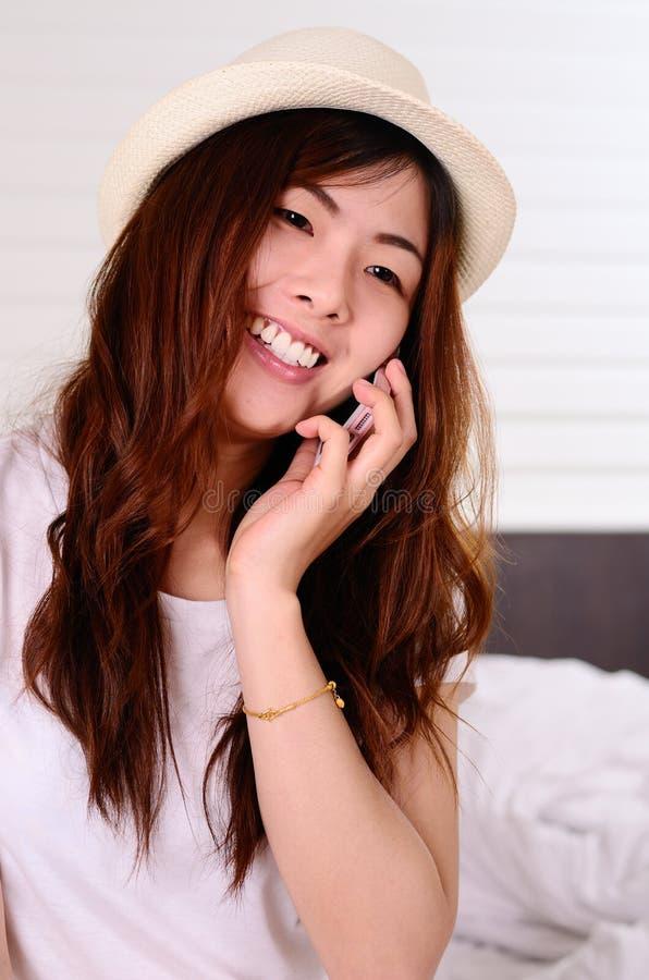 Parler et causerie adolescentes asiatiques avec le téléphone portable images stock