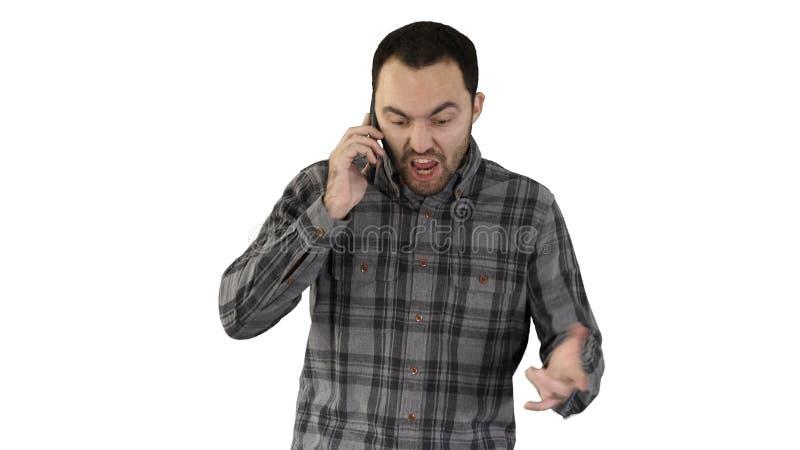 Parler fâché d'homme au téléphone et marche sur le fond blanc photo stock