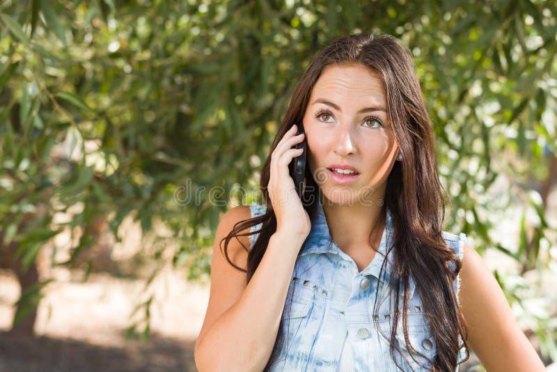 Parler femelle de l'adolescence de métis malheureux au téléphone portable dehors photo libre de droits