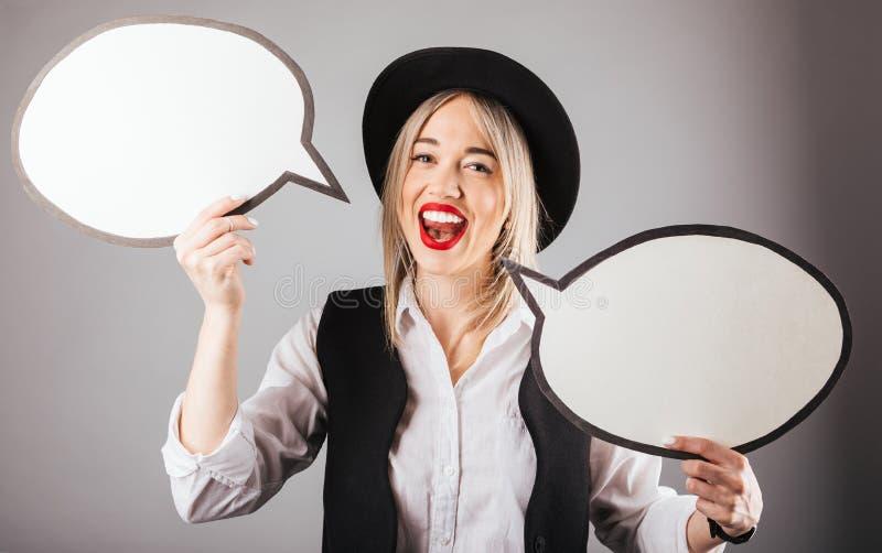 Parler heureux Femme blonde dans le chapeau noir tenant des bubles de la parole de conversation sur le fond gris image stock