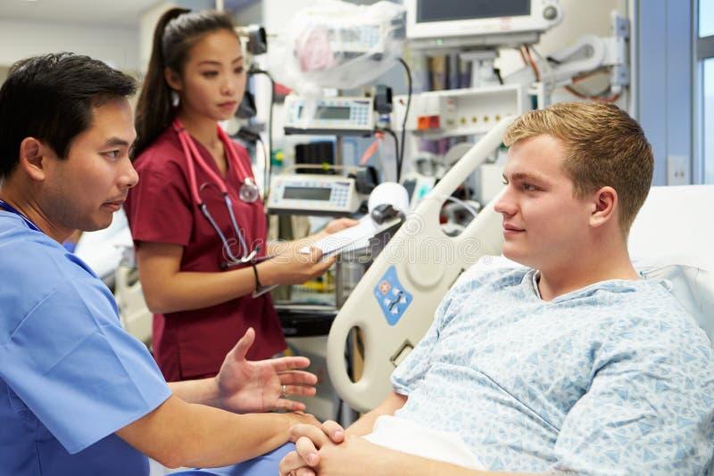 Parler patient masculin au personnel médical dans la chambre de secours image libre de droits