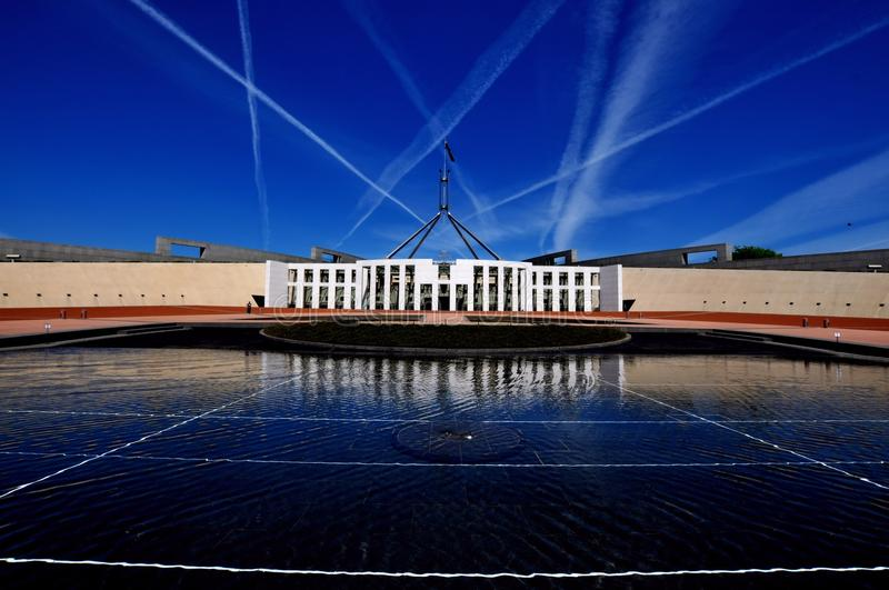 Parliament House Canberra Australia front view. Parliament House Canberra Australia wide shot from front and jet streams in sky stock image
