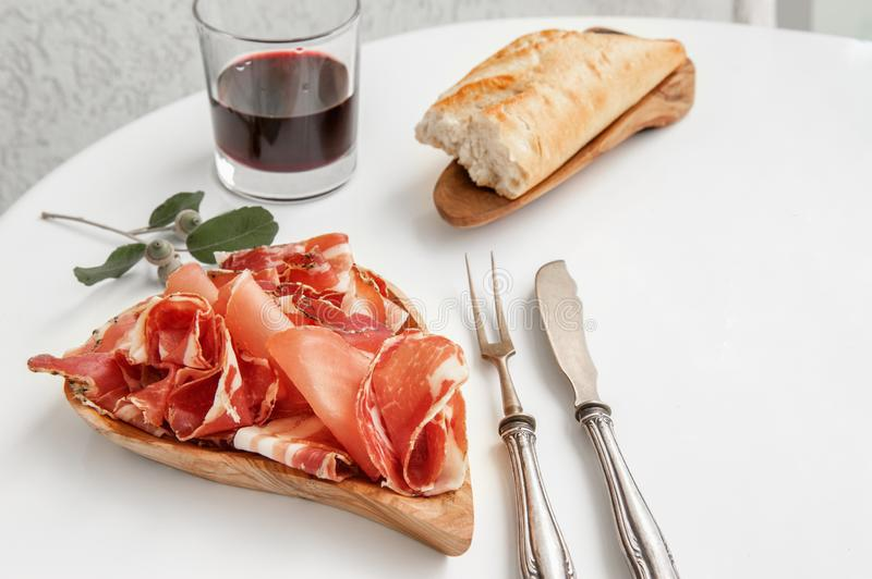 Parma flavored ham in spices, thinly sliced on a white table with red wine bread and antique cutlery stock image
