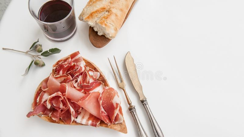 Parma flavored ham in spices, thinly sliced on a white table with red wine bread and antique cutlery royalty free stock photo