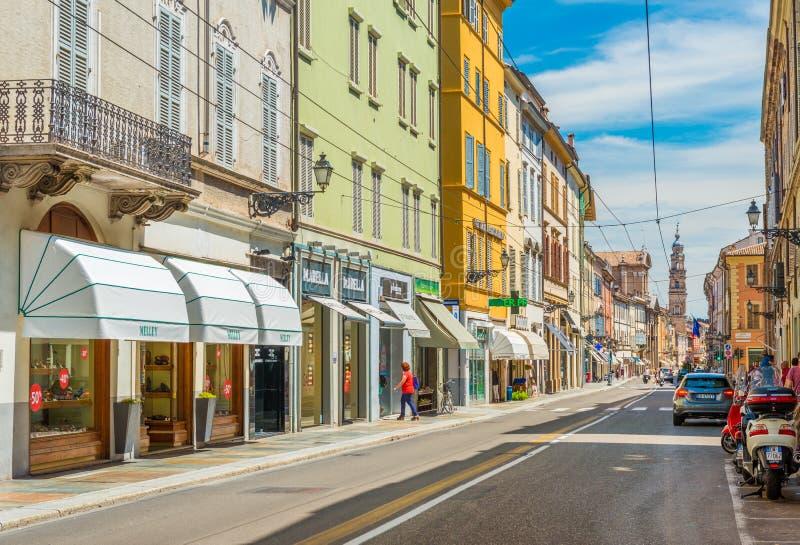 Parma Italien: En gata av Parma med historiska byggnader, shoppar, apotek, den parkerade bilen och sparkcykeln royaltyfria bilder