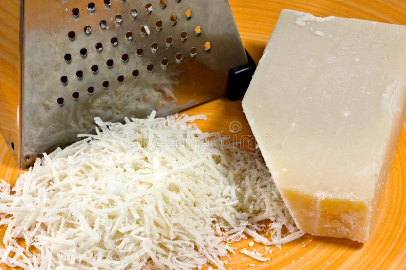 Parmesan cheese. Grated parmesan cheese with grater on an orange plate stock images