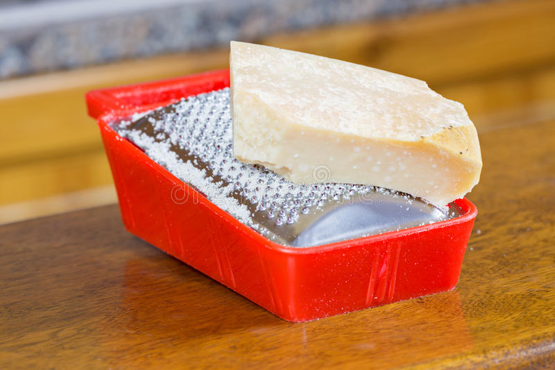 Parmesan cheese on grater. Parmesan cheese grater in the kitchen stock image