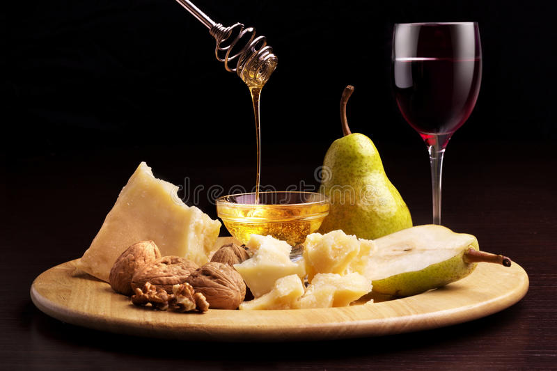 Parmesan cheese pears honey walnuts and wineglass stock image