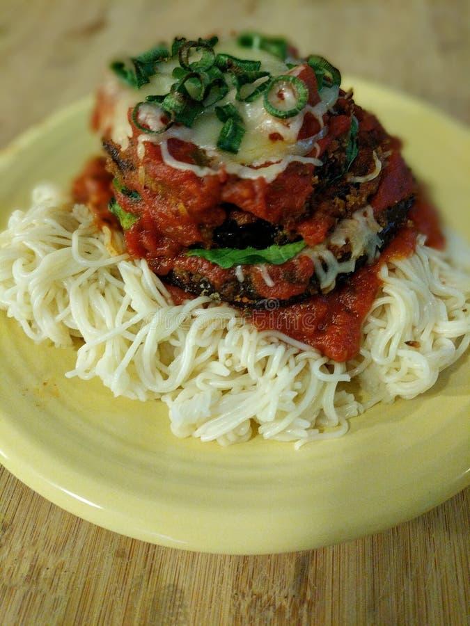 Parmesan cuit au four et posé d'aubergine servi placé sur Angel Hair Pasta images libres de droits