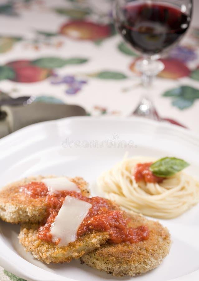 Parmesan d'aubergine de Vegan avec les pâtes et le vin rouge photographie stock