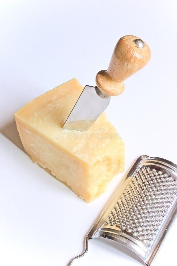 Parmesankäse mit Messer und Raspel lizenzfreies stockbild