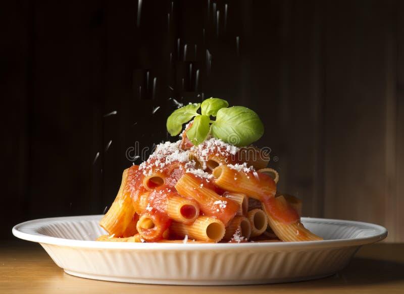 Parmesankäseparmesankäse auf dem Makkaroni mit Tomatensauce stockbild