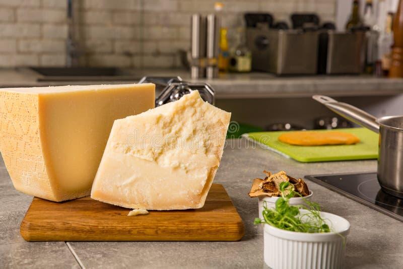 Parmesankäseparmesankäse auf Schneidebrett mit Basilikum und Messer auf hölzernem Hintergrund stockfotos