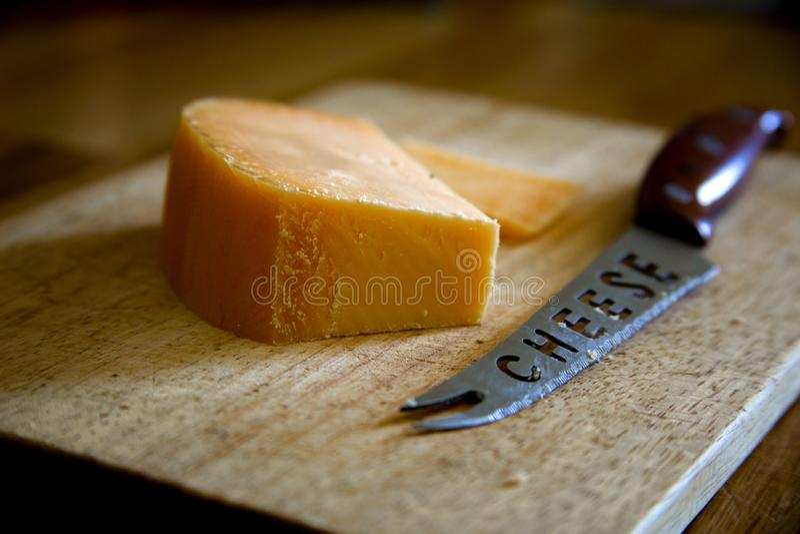Parmesankäseparmesankäse mit Messer auf Schneidebrett auf hölzernem Hintergrund lizenzfreie stockfotos