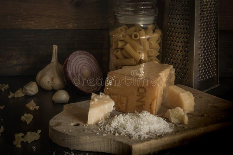 Parmesankäseparmesankäsestück auf hölzernem Brett Zerriebener Parmesankäseparmesankäse mit Olivenöl, Knoblauch und Teigwaren Der  stockfotografie