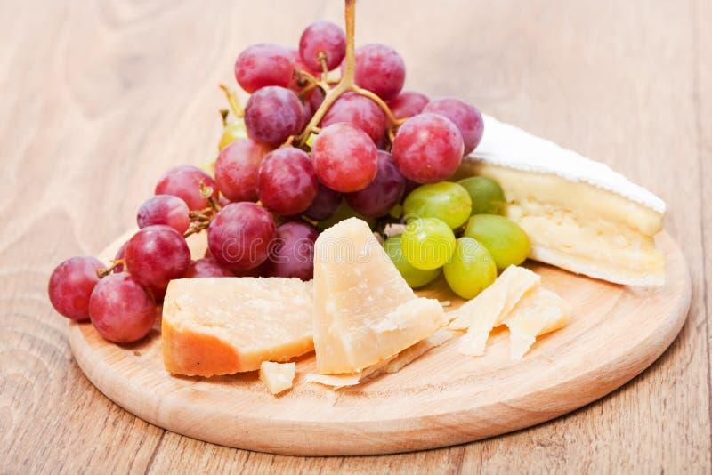 Parmesano y brie del queso con la uva fotos de archivo