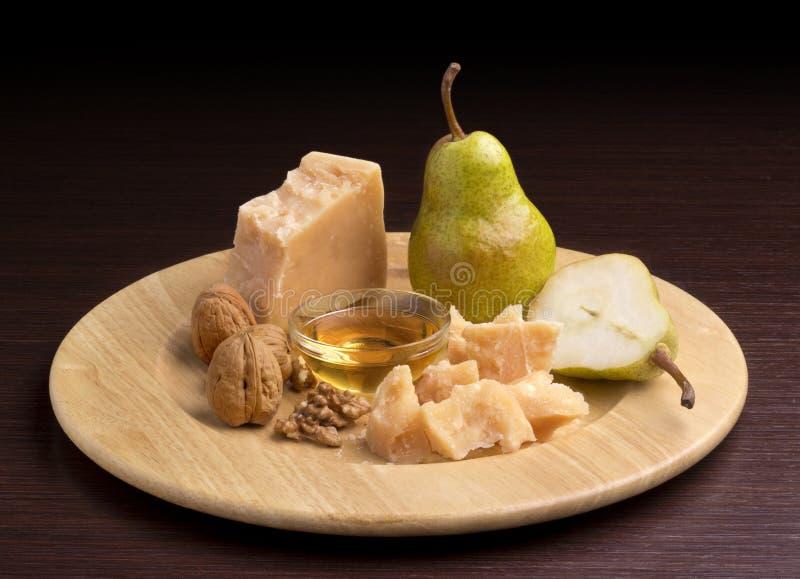 Parmesanost med honung och päron arkivfoto
