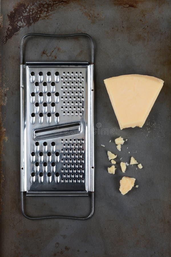 Parmesanost och rivjärn arkivfoto
