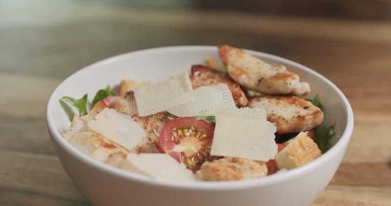 Parmezaanse kaasvlokken die op caesar salade vallen royalty-vrije stock foto