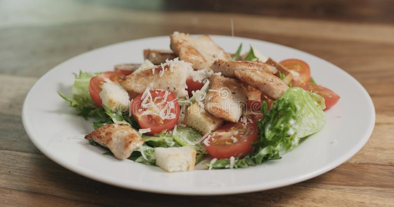 Parmezaanse kaasvlokken die op caesar salade vallen royalty-vrije stock afbeelding