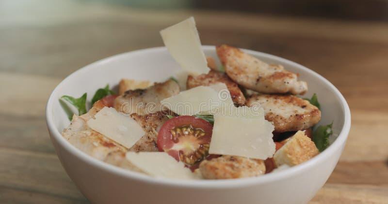 Parmezaanse kaasvlokken die op caesar salade vallen royalty-vrije stock foto's