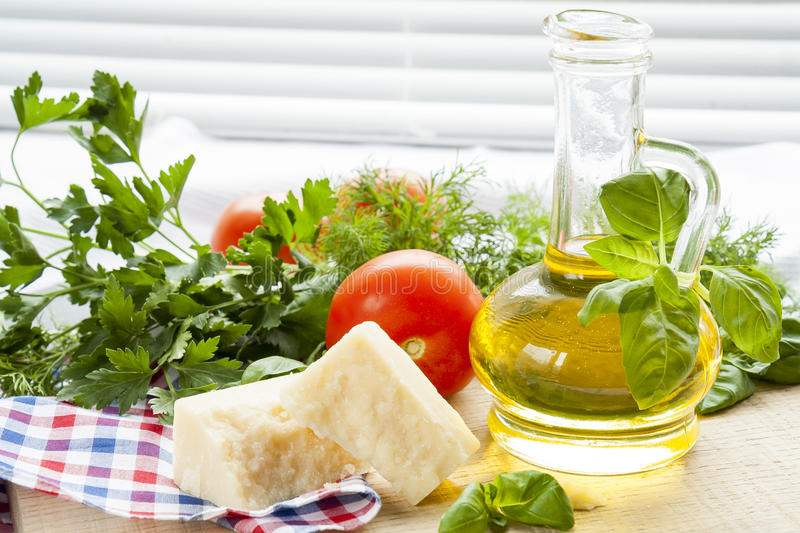 Parmigiano cheese, olive oil herbs and tomatoes on wooden background stock image