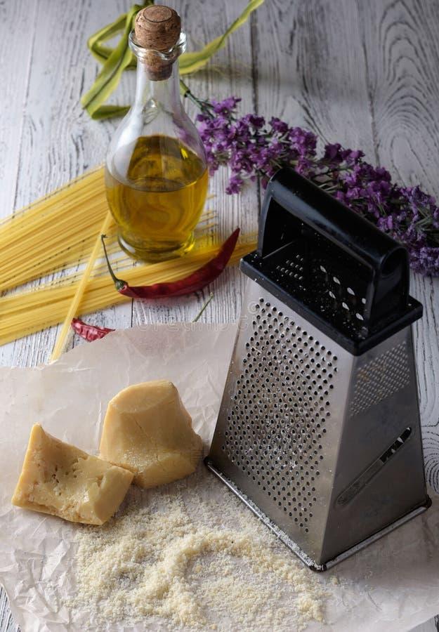 Parmigiano grattato, bottiglia di olio d'oliva e grattugia del metallo sopra fotografia stock libera da diritti