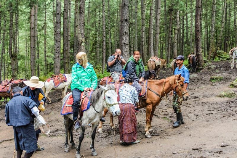Paro, Bhutan - September 18, 2016: Tourists on horses towards Taktshang Palphug Monastery (the Tiger's Nest), Bhutan. Paro, Bhutan - September 18, 2016: Tourists stock photo