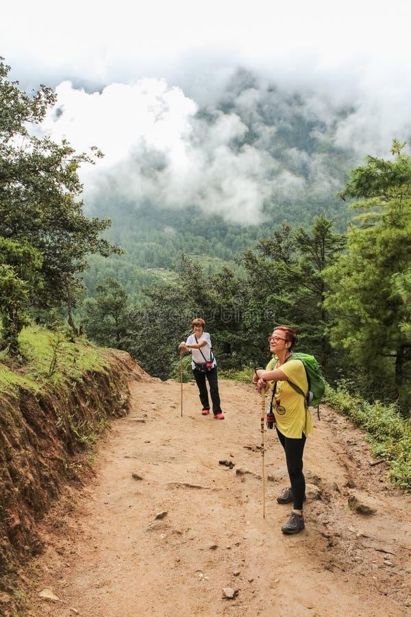 Paro, Bhutan - September 18, 2016: Two tourist women hiking on the way to Taktshang Palphug Monastery (the Tiger's Nest), Bhutan. Asia royalty free stock photography