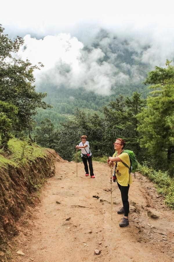 Paro, Butão - 18 de setembro de 2016: Duas mulheres do turista que caminham na maneira ao monastério de Taktshang Palphug (o ninh fotografia de stock royalty free
